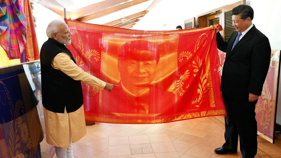 Prime Minister Narendra Modi presents a hand-woven portrait to Chinese President Xi Jinping at Mahabalipuram.